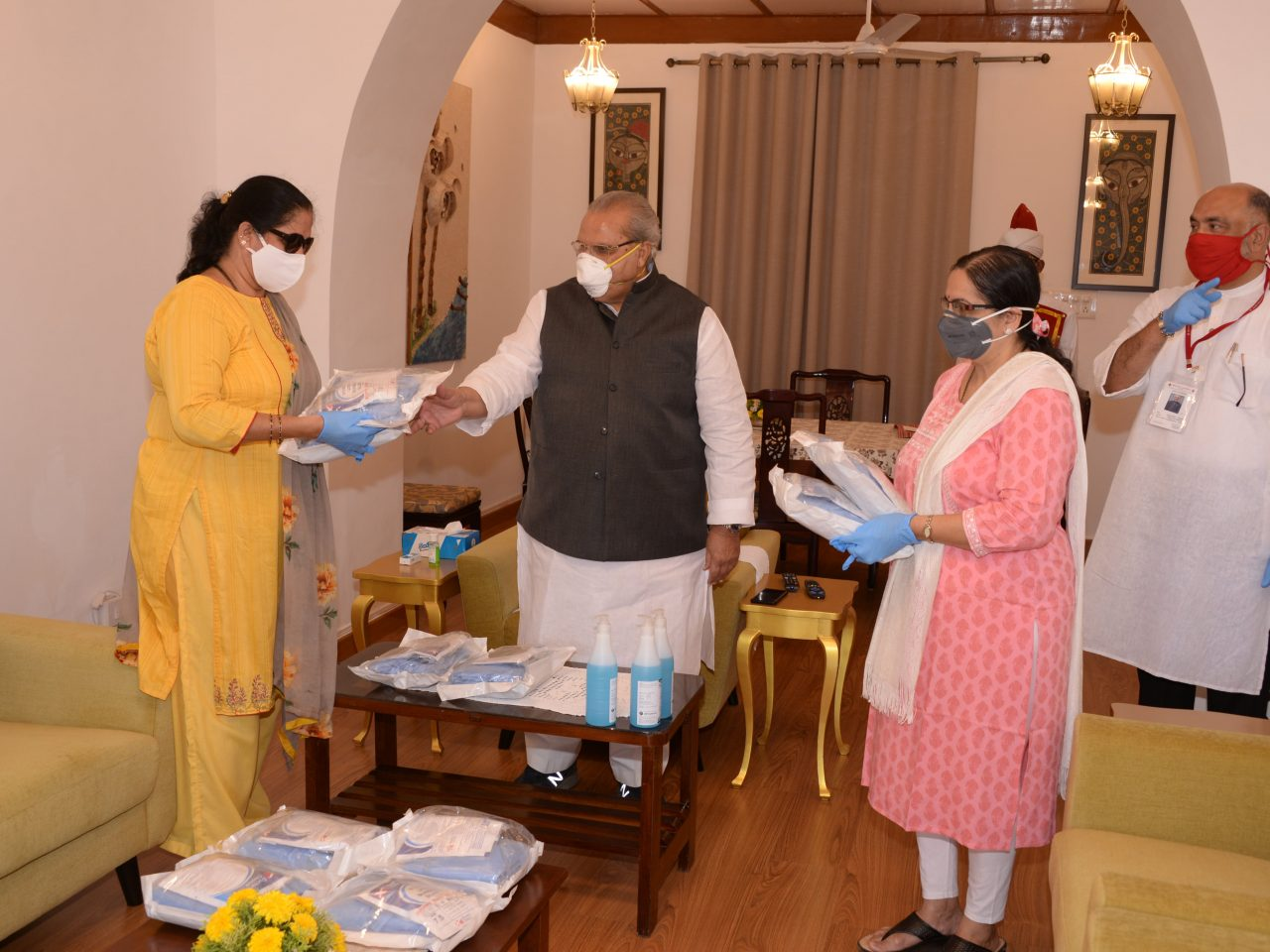 Members of Rotary Club handing over the PPE kits to Hon'ble Governor for the use of health care givers.