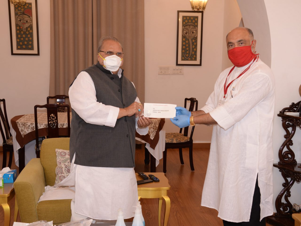 Shri Satya Pal Malik, Governor of Goa handing over a cheque of Rs. 3 Lakhs from the Governor's Discretion fund to Shri Gaurish Dhond, Chairman, Indian Red Cross Society, Goa Branch, to fight against the pandemic of Covid-19